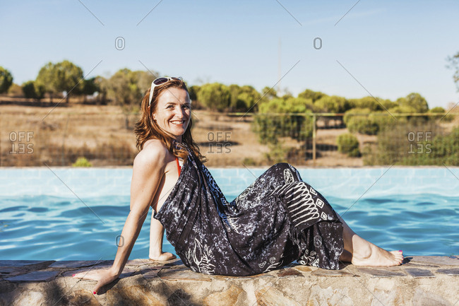 Side view portrait of smiling mid adult woman wearing sarong sitting at poolside on sunny day