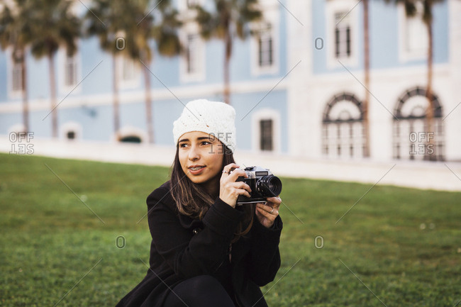 Mid adult woman with camera looking away while sitting on grass against building