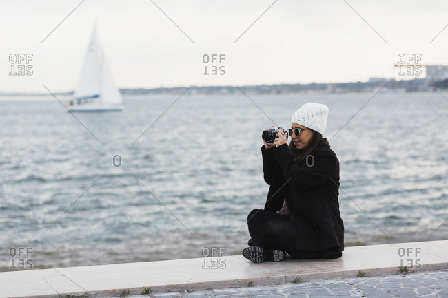 Full length of woman sitting on promenade photographing by water, Lisbon, Portugal