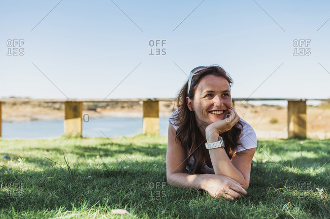 Happy woman lying on grass against sky