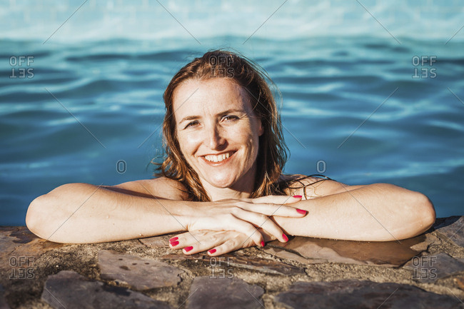 Portrait of happy woman at poolside on sunny day