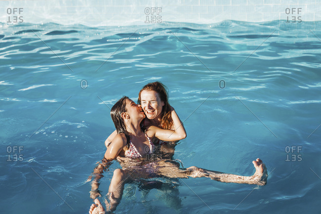 High angle view of girl kissing happy mother in swimming pool