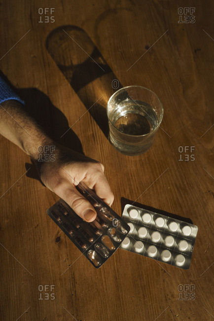 Cropped hand of man holding medicine blister pack by drinking water on table at home