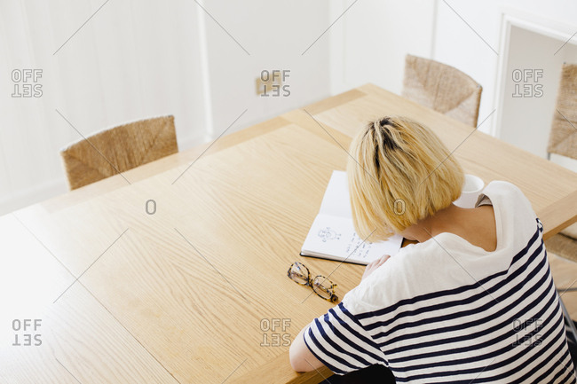 High angle view of woman with short hair writing in diary at table
