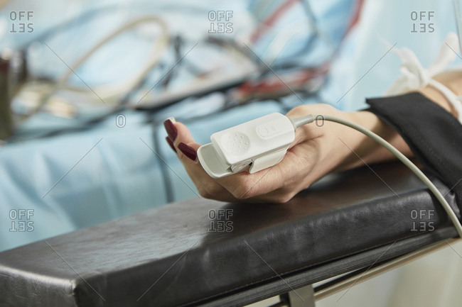 Cropped image of patient wearing pulse oxymeter while lying on bed at hospital