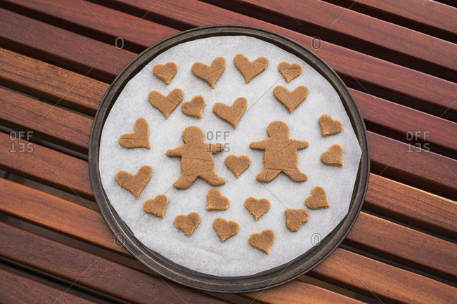 Gingerbread couple surrounded by hearts in baking sheet on table