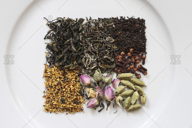Directly above view of dried herbs, spices, tea leaves, and flowers on plate