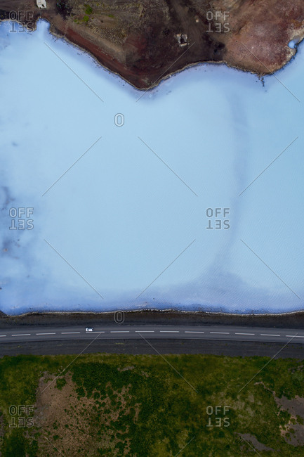 Drone view of road amidst field and lake, Myvatn, Iceland