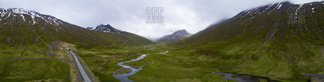 Panoramic view of road by stream on green landscape against sky, Iceland