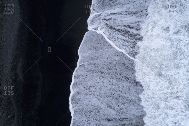 Drone view of surf on shore at beach with black sand, Iceland