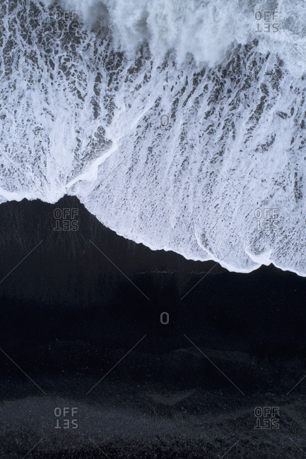 Aerial view of surf on shore at beach with black sand, Iceland