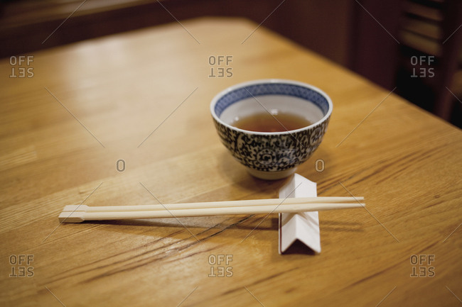 Close-up of chopsticks and bowl on wooden table