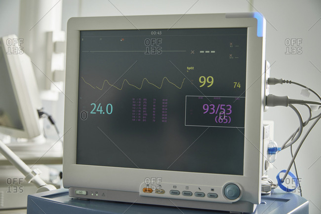 Close-up of monitoring equipment with medical data on screen in hospital ward