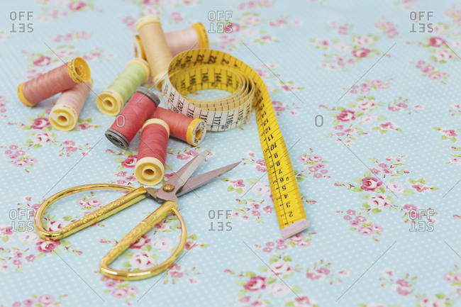 Close-up of various spools and scissors with tape measure on blue fabric