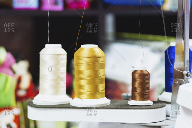Close-up of various spools on sewing machine