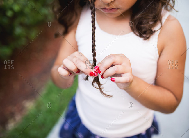 Young girl braiding her hair