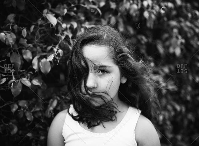 Black and white portrait of young girl with hair blowing in her face