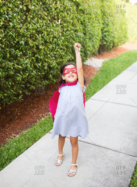 Little girl dressed as a super hero holding fist in the air