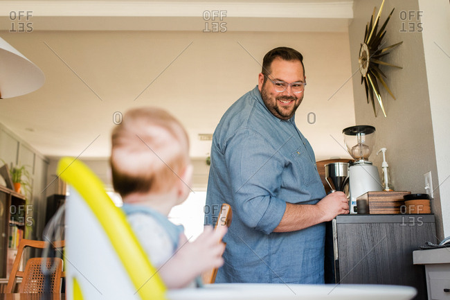 Father smiling at baby in high chair
