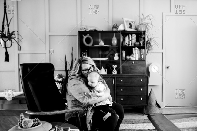 Mother holding baby and kissing her head in black and white