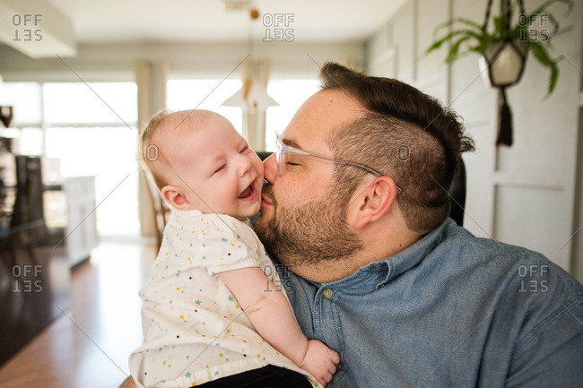 Father holding baby and kissing her cheek