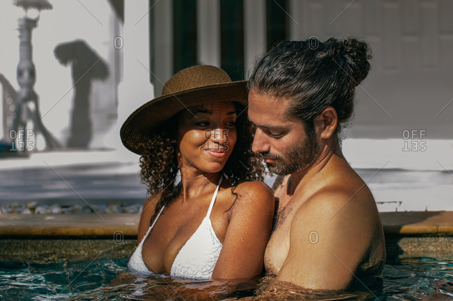 Young mixed race woman looking lovingly at boyfriend while standing in swimming pool