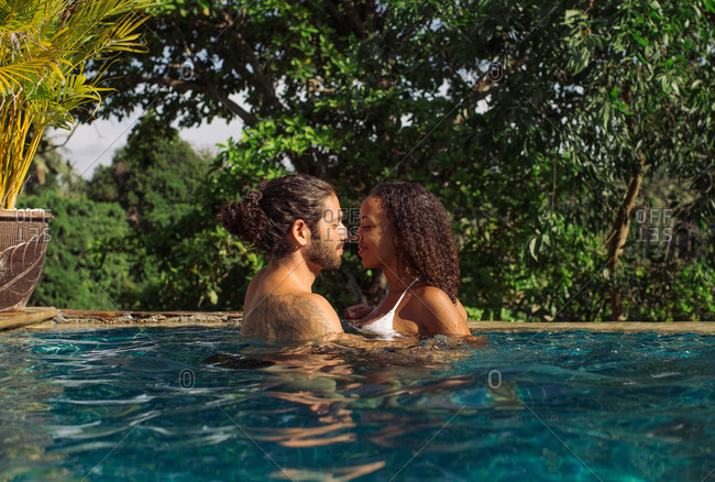 Young mixed race couple looking lovingly at each other while hugging in swimming pool
