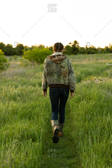Rearview of young woman walking along path through fields at sunset in Austin, Texas