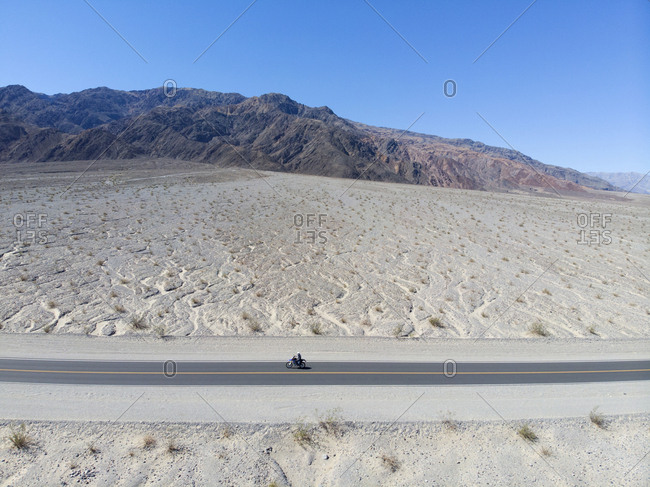 Aerial view of solo motorcyclist riding through parched landscape of Death Valley, California