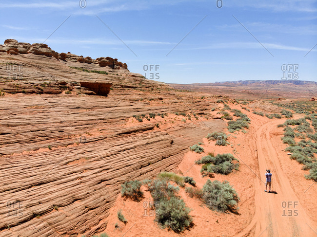 High angle view of tourist taking photograph of sandstone formation in Monument Valley National Park, Utah