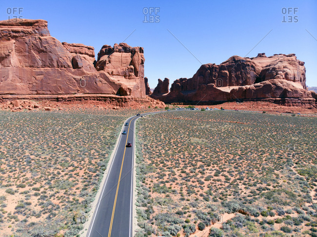 Aerial view of Cars travelling along perfect black top road disappearing into sandstone rock formations in Arches National Park, Utah