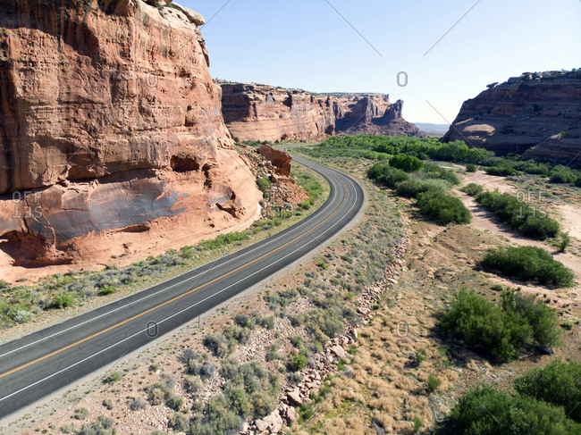 Aerial view of ribbon of tarmac road curving round sandstone cliffs in Canyonlands National Park, Utah
