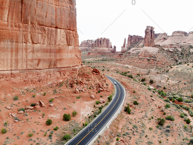 Bird's eye of solitary car on road curving around red hued buttes in Arches national Park, Utah