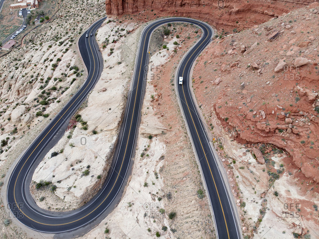 Bird's eye view of cars driving along switchback roads winding up side of valley in Arches National Park, Utah