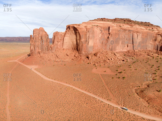 Aerial view of vehicles driving by iconic butte along dirt road in Monument Valley, Arizona