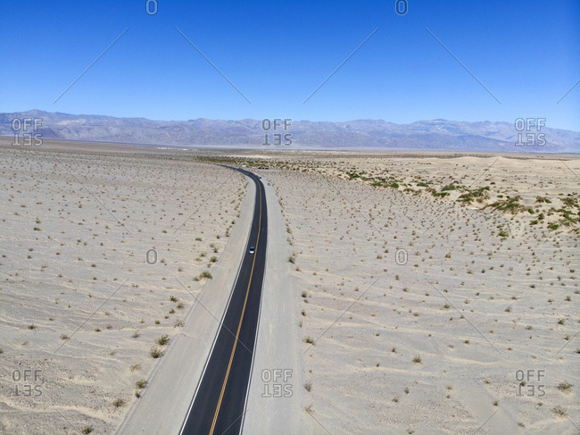 Aerial view of single car on highway curving towards mountains on horizon in Death Valley, California