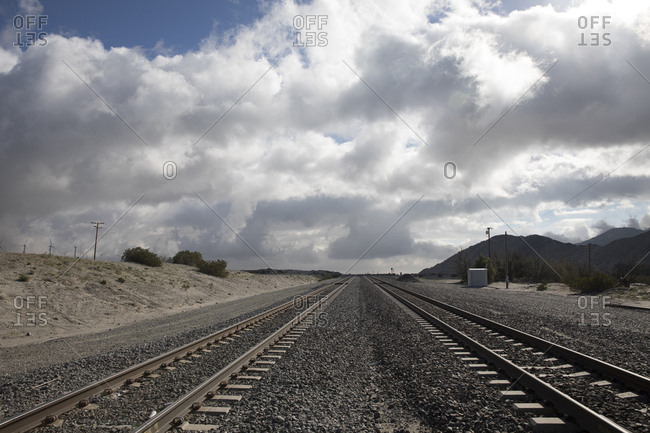 Two sets of railway tracks disappear into the desert in Palm Springs, California
