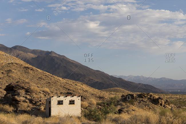 Small cinderblock hut nestled into foot hills in desert of Palm Springs, California