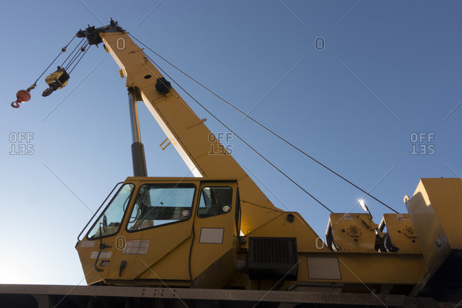 Low angle view of construction crane against blue sky