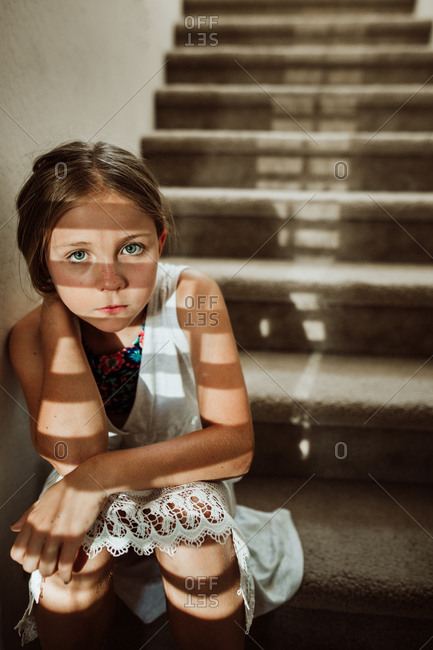 Girl sitting on step at base of staircase