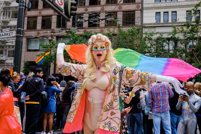 San Francisco, California, USA - June 25, 2017: Person with curlers in hair waving rainbow flag at San Francisco Pride Parade