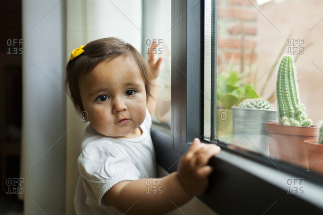 Baby standing next to window