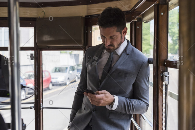 Businessman using mobile phone while traveling in bus