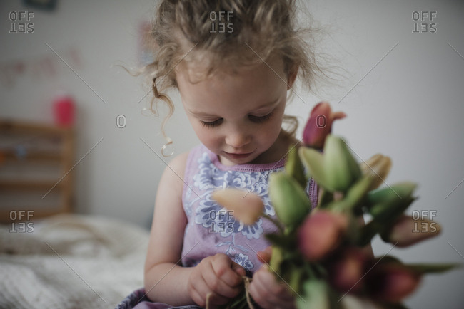 Close-up of girl holding tulips while sitting on bed at home