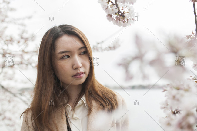 Close-up of thoughtful woman standing by lake against sky during springtime