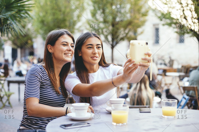 Female friends taking selfie with instant camera while sitting at sidewalk cafe
