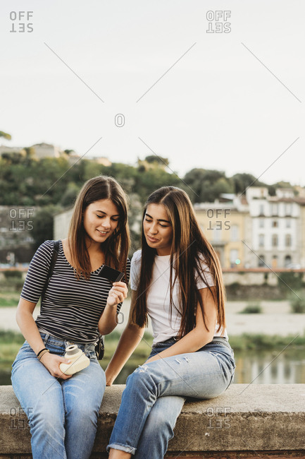 Friends looking at instant photograph while sitting on retaining wall by Arno river against clear sky