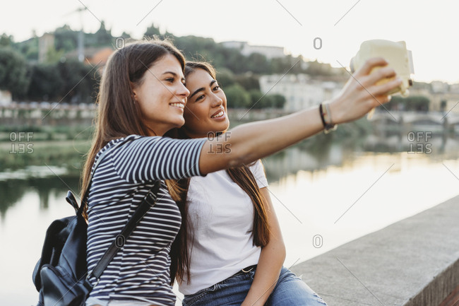 Friends taking selfie with instant camera while sitting on retaining wall by Arno river in city