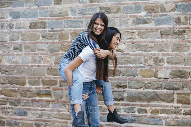 Happy woman piggybacking friend while standing by wall