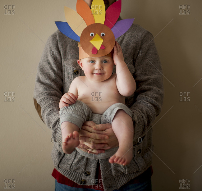 Portrait of cute shirtless son wearing colorful paper headdress while being carried by father against wall at home